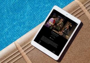 Ein Tablet liegt am Rand eines Pools