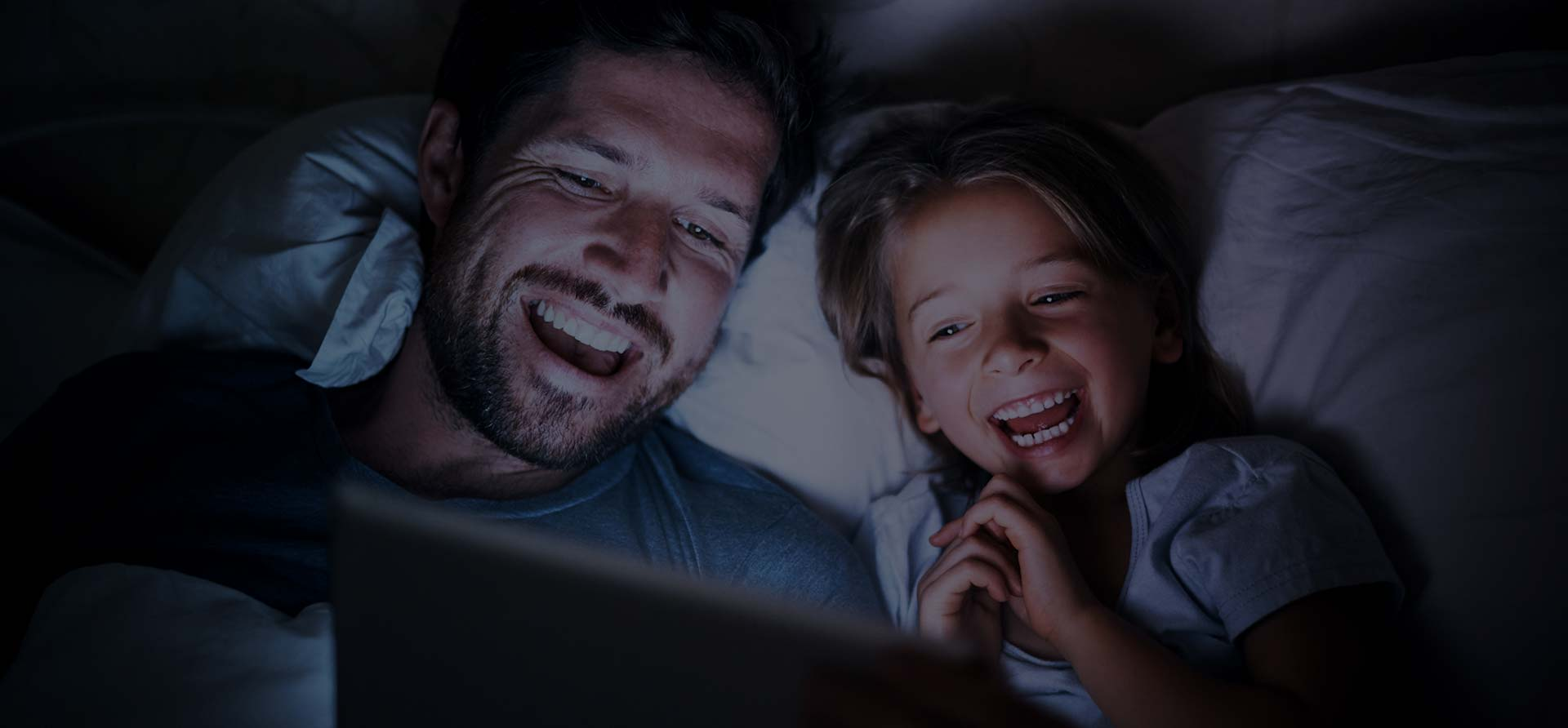 Vater und Tochter schauen auf dem Tablet