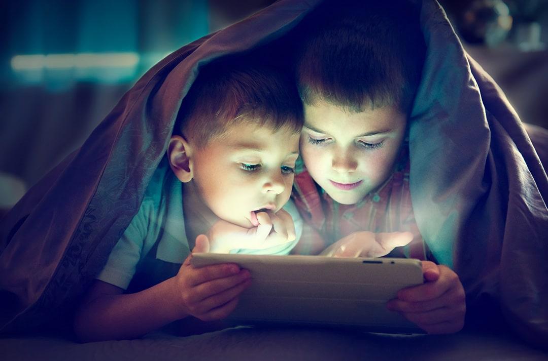 Zwei Jungs schauen gemeinsam fern auf einem Tablet.