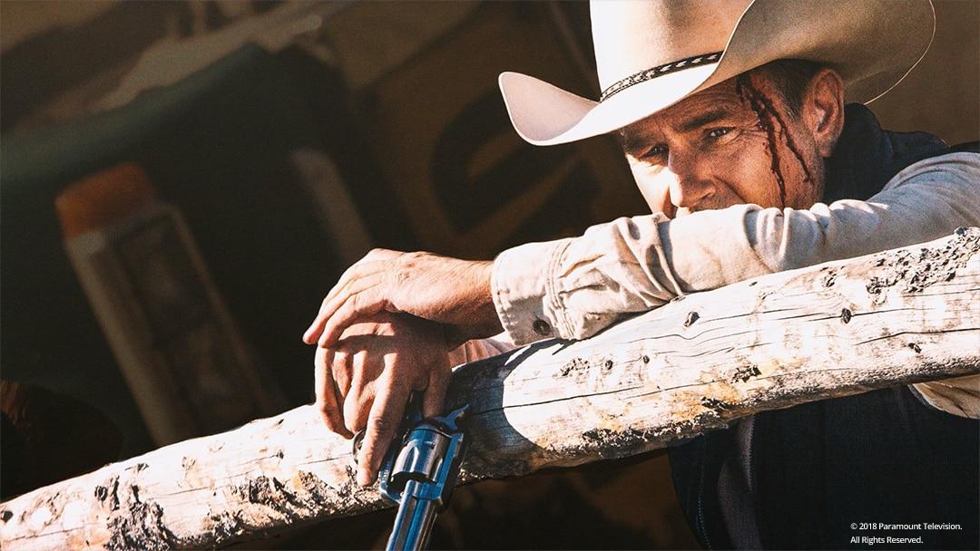 Kevin Costner lehnt sich an einen Holzzaun